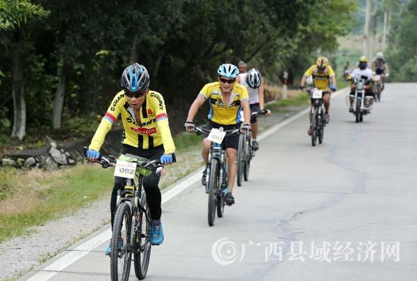 图2:7月23日,209国道广西柳州市融安县大良镇路段,参赛选手在比赛中骑行。(谭凯兴 摄).JPG