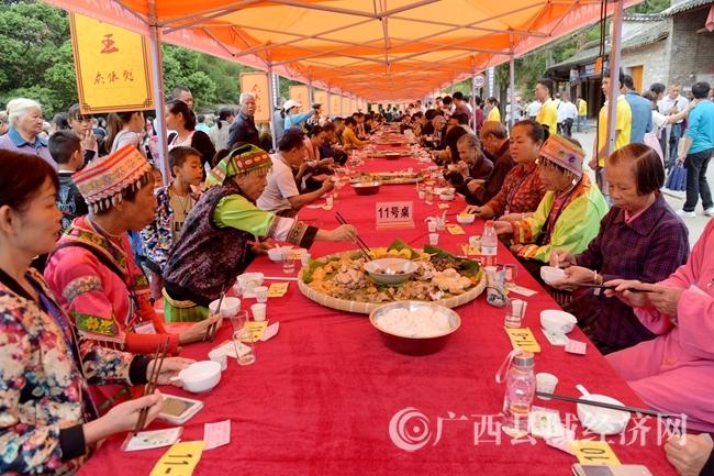 在长寿簸箕宴现场,游客与长寿老人一起品长寿美食。