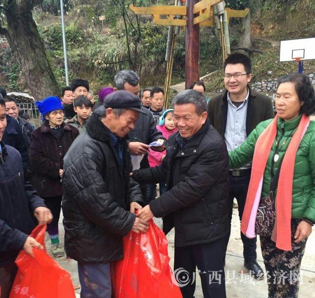 融水县政协副主席何来源(右二)给贫困户发放捐赠物品mmexport1484833795353