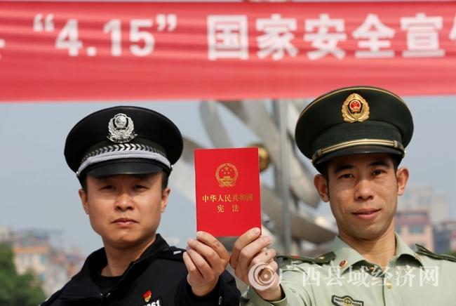 图8:4月14日,在广西柳州市融安县长安广场,两名工作人员展示向市民发放的《宪法》宣传品。(谭凯兴 摄)