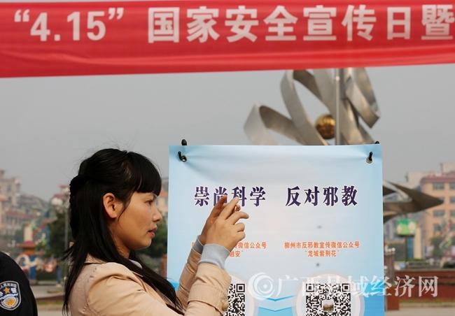 图2:4月14日,在广西柳州市融安县长安广场,一名市民在了解国家安全相关法律法规。(谭凯兴 摄)