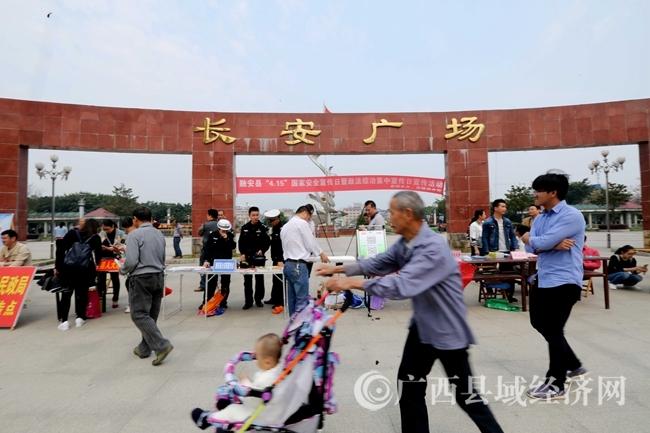 图11:4月14日,在广西柳州市融安县长安广场,一名市民推着小孩在宣传台前经过。(谭凯兴 摄)
