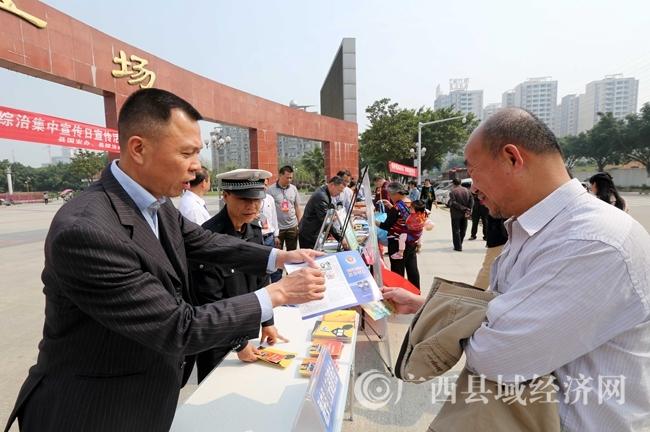 图10:4月14日,在广西柳州市融安县长安广场,工作人员(左)向市民讲解国家安全知识。(谭凯兴 摄)