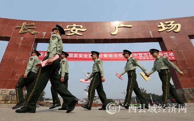 图1:4月14日,在广西柳州市融安县长安广场,武警战士拿宣传资料准备向市民宣传法律法规。(谭凯兴 摄)