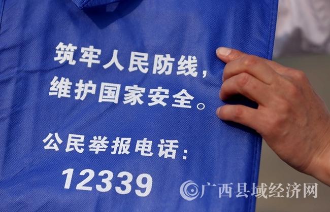 图7:4月14日,在广西柳州市融安县长安广场,工作人员为市民发印刷有国家安全知识的环保宣传袋。(谭凯兴 摄)