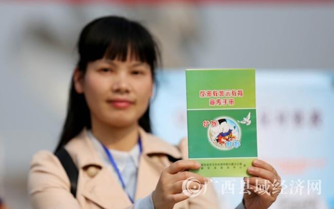 图6:4月14日,在广西柳州市融安县长安广场,一名市民展示领取的宣传品。(谭凯兴 摄)