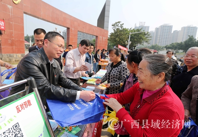 图9:4月14日,在广西柳州市融安县长安广场,工作人员向市民发放国家安全知识宣传品。(谭凯兴 摄)