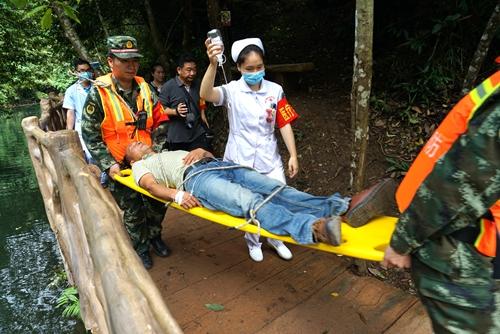 """图一:5月25日,在融水苗族自治县双龙沟原始森林景区,救援队伍在对一""""受伤游客""""进行紧急救援。.JPG"""