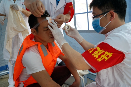 """图五:5月25日,在融水苗族自治县双龙沟原始森林景区,医护人员正在对一""""受伤游客""""进行伤口包扎。.JPG"""