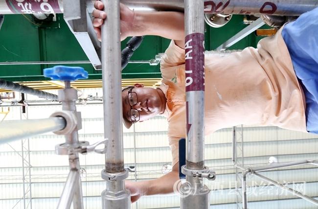 图7:7月26日,广西仙草堂制药有限责任公司工人在青蒿素提炼车间检查保养设备。(谭凯兴 摄)