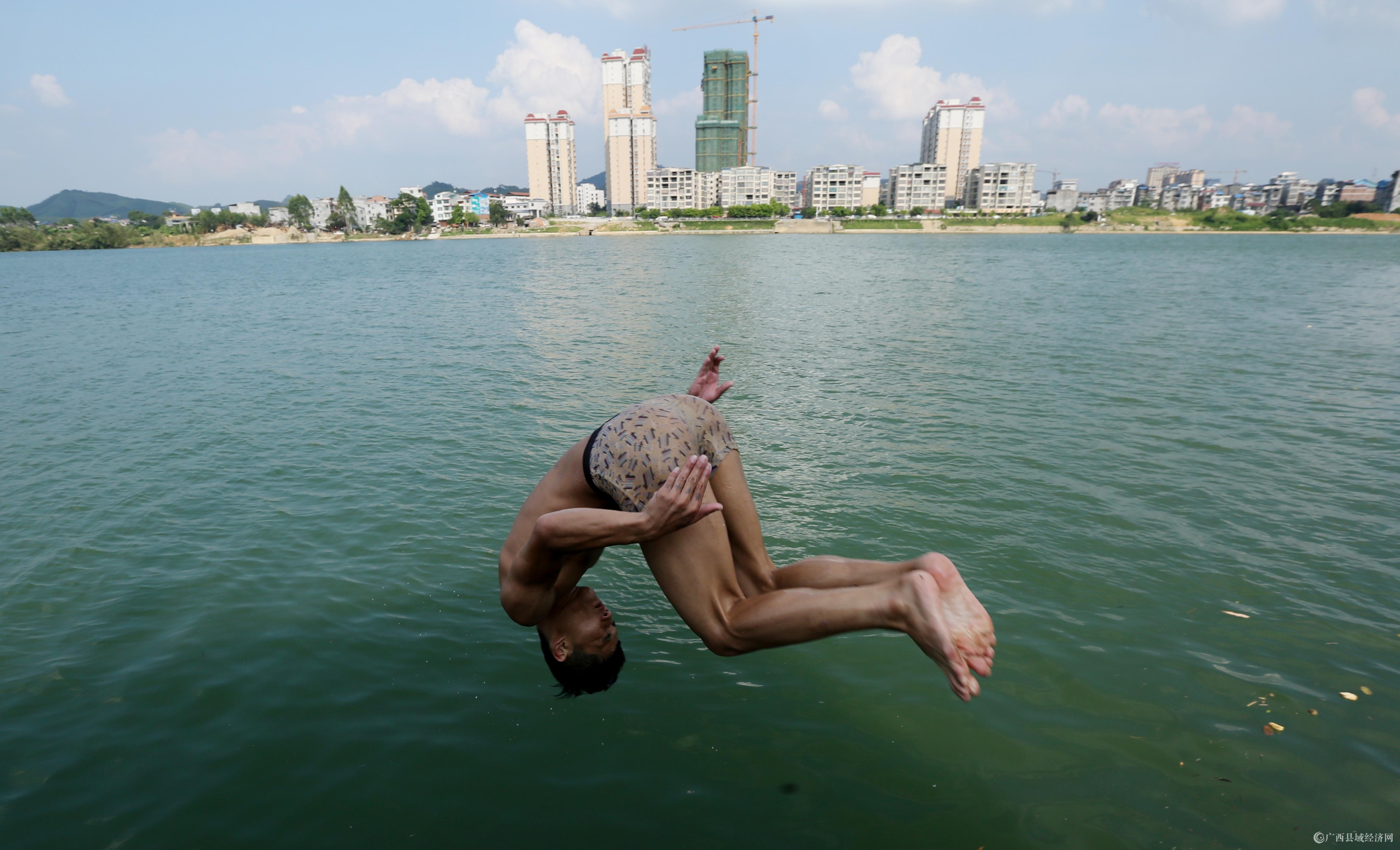 图5:8月7日,在融江广西柳州市融安县城段,一名青年跳入水中解暑。(谭凯兴 摄).JPG