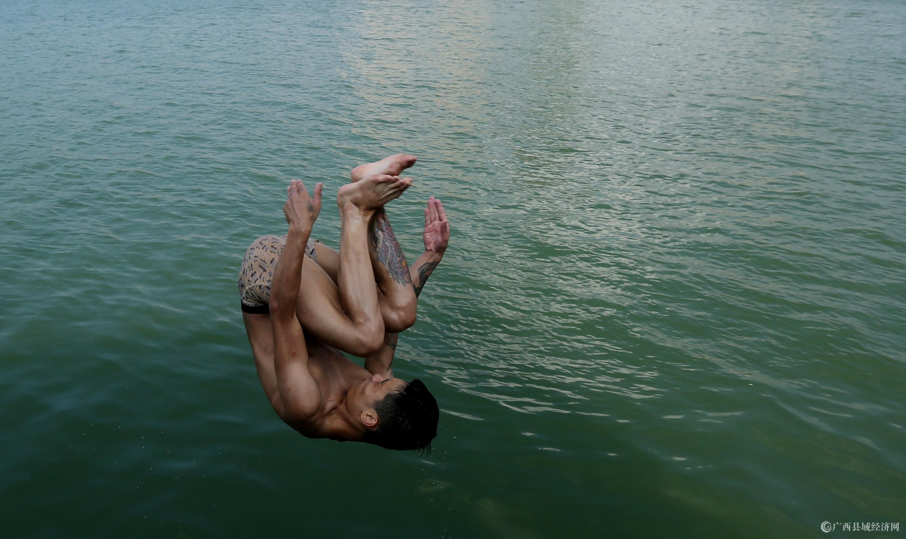 图6:8月7日,在融江广西柳州市融安县城段,一名青年跳入水中解暑。(谭凯兴 摄).JPG