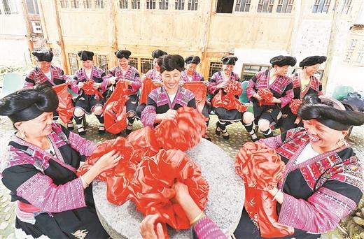 龙胜龙脊镇黄洛瑶寨:瑶嫂们为即将参军入伍的新兵制作大红花
