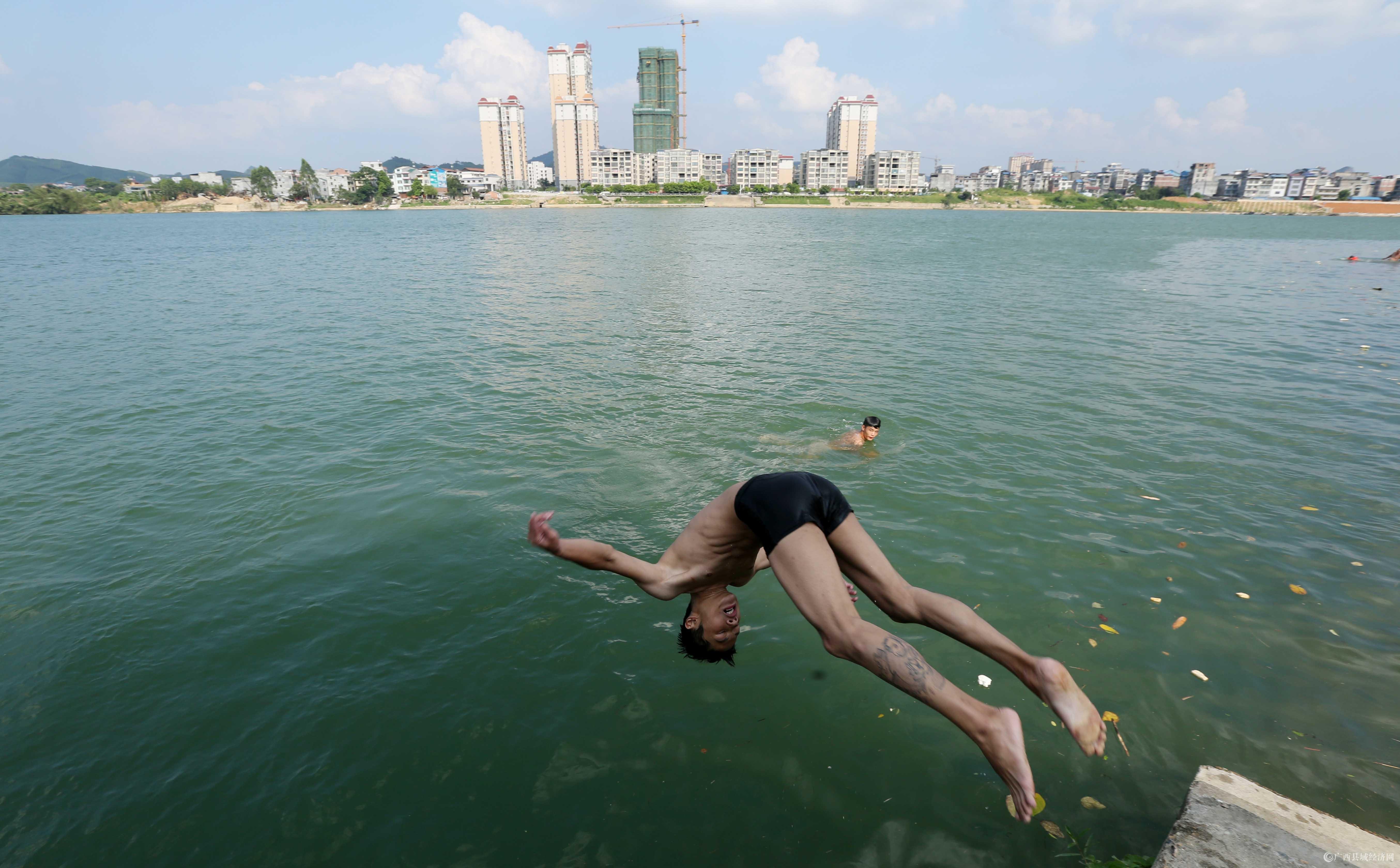 图7:8月7日,在融江广西柳州市融安县城段,一名青年跳入水中解暑。(谭凯兴 摄).JPG