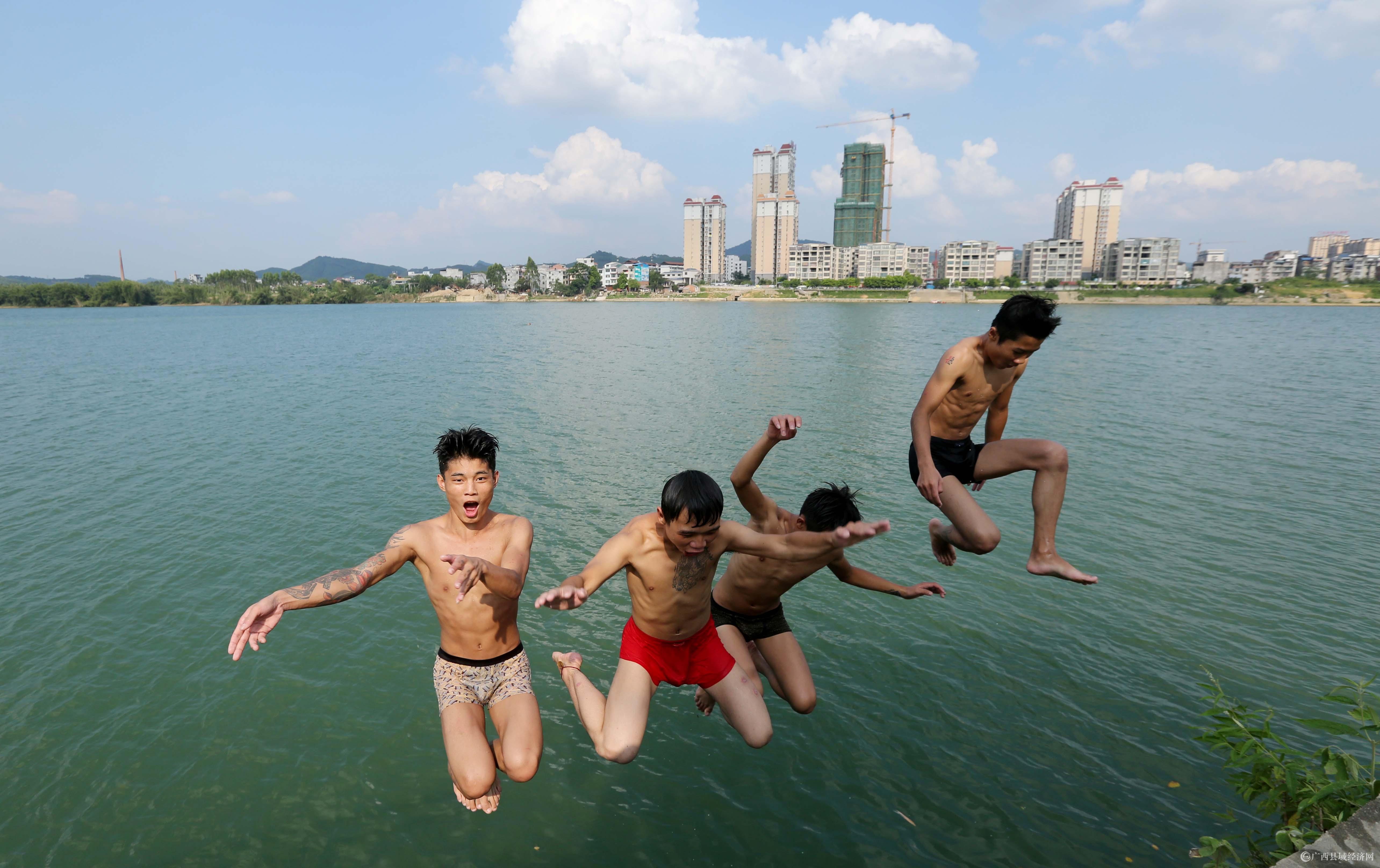 图1:8月7日,在融江广西柳州市融安县城段,一群青年跳入水中解暑。(谭凯兴 摄).JPG