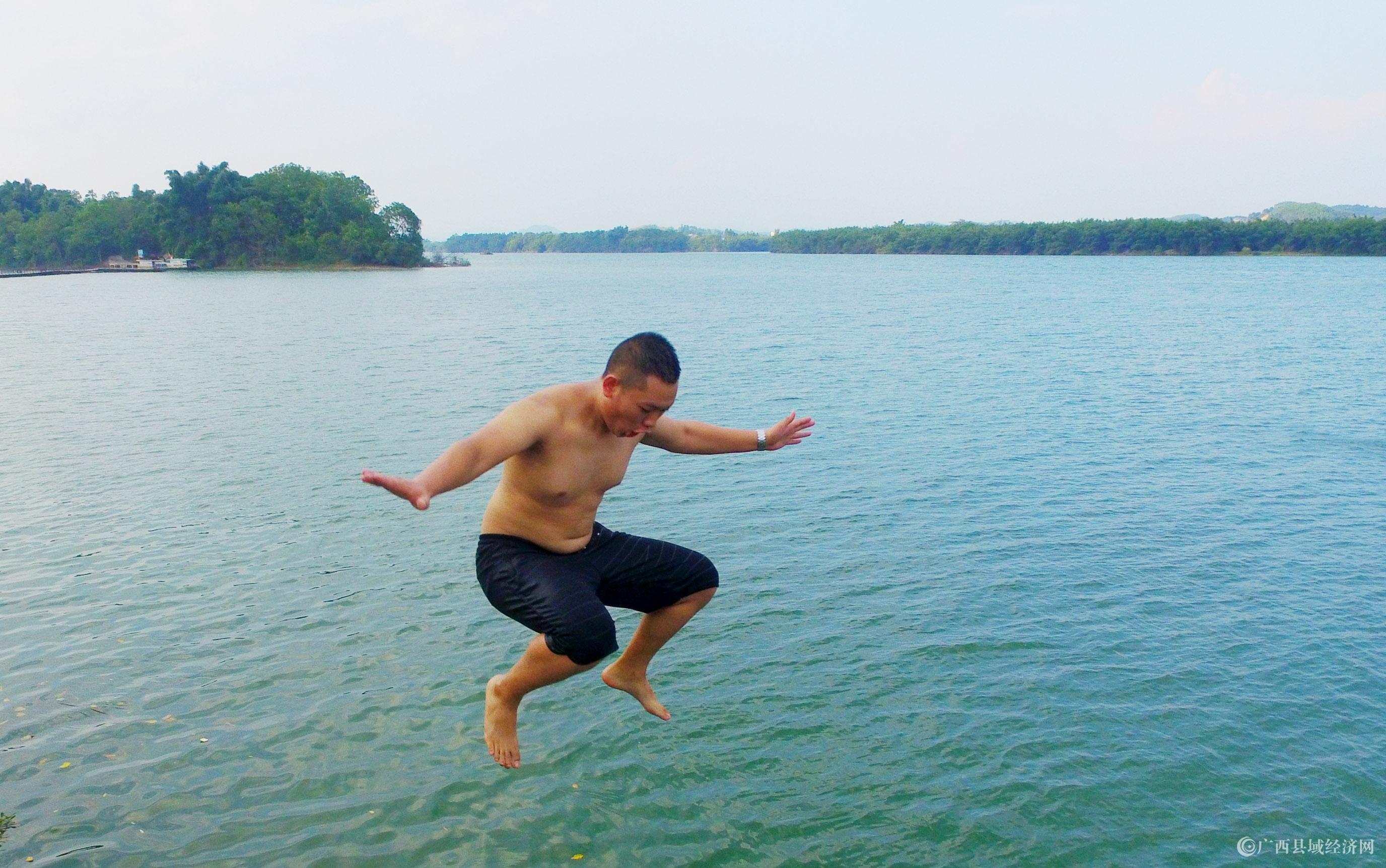 图3:8月7日,在融江广西柳州市融安县城段,一名青年跳入水中解暑。(谭凯兴 摄).JPG