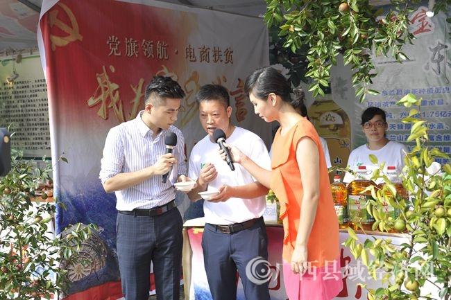 采访现场,主持人听取商家介绍东兰山茶油的特点及生产流程(韦禄东 摄)