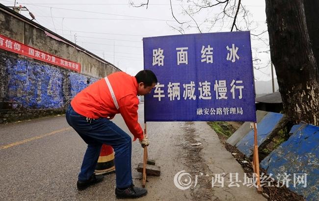 图5:1月27日,在国道357线广西柳州市融安县浮石镇路段,公路养护站工人韦贵华中路口放置路面结冰提醒标识牌。(谭凯兴