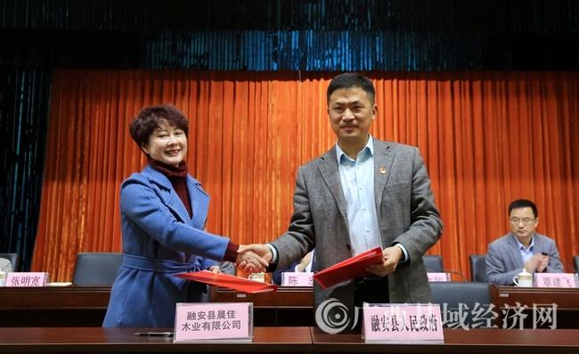 图3:融安县县长陈文敏(右)与企业代表签订投资协议后握手。(谭凯兴 摄).JPG